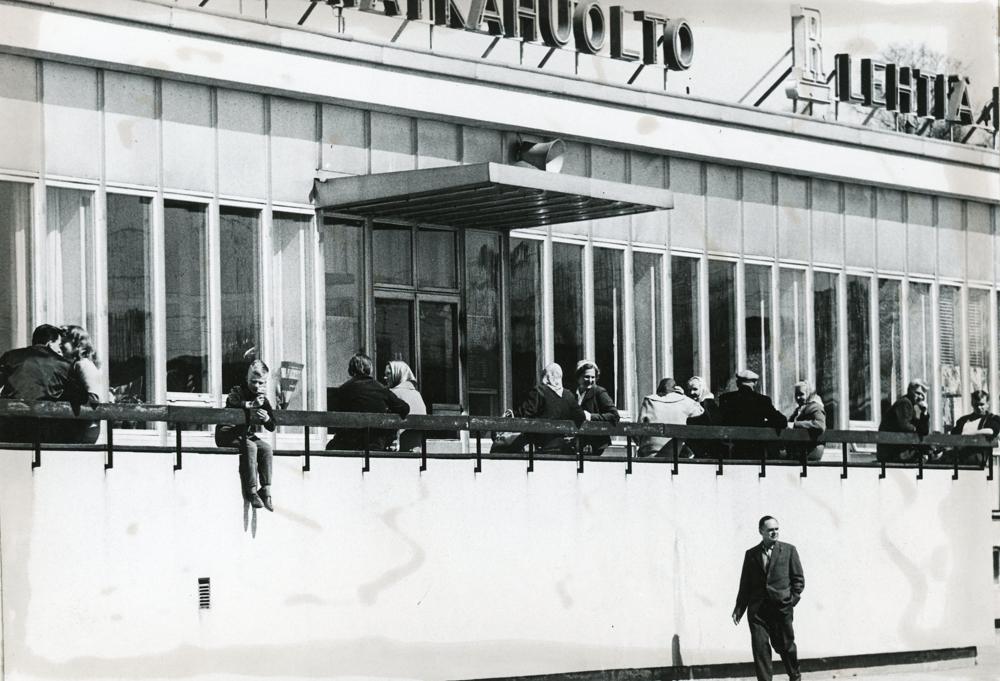 Riihimäen linja-autoaseman terassilla kaikenikäiset nauttivat aurinkoisesta kevätpäivästä. Kuva Erkki Vaalle 1960-luvun alku, RKM-kokoelmat.