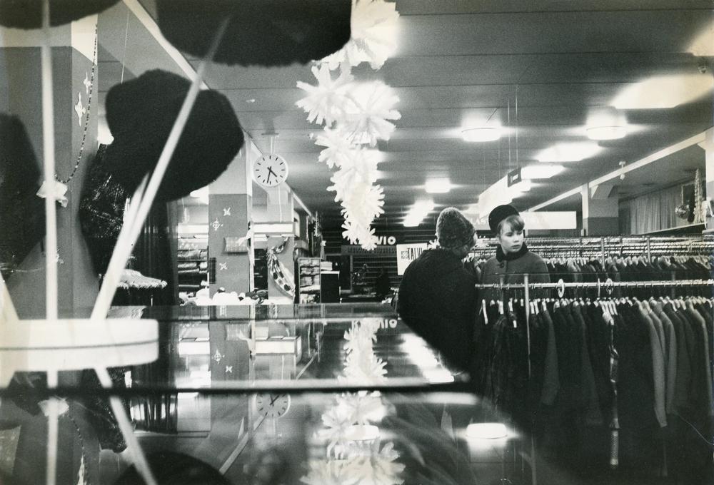 Tytöt Sokoksen toisessa kerroksessa talvitakkiostoksilla 1960-luvun alussa. Taustalla näkyy tavaratalon yhteydessä ollut baari. Kuva Arvo Haakana, 1960-luvun alku. RKM-kokoelmat.